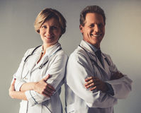 Beautiful mature doctors. In white coats are looking at camera and smiling while standing with crossed arms on gray background Stock Image