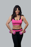 Beautiful Mature Female Athlete. A lovely mature woman with remarkable abdominal musculature and wearing fitness wear, holds a pair of pink hand weights Stock Photo