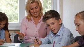 Beautiful mature female teacher helping her students in class stock images