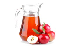 mature fresh red apple with green leaves and apple juice in a jar on a white isolated background royalty free stock photos