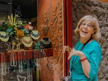 Beautiful mature happy tourist woman stays smiling at jewelry show-window. Beautiful mature happy tourist woman with old video camera on her neck travelling in Stock Photo