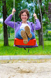 Beautiful mature happy white woman swing playground Stock Images