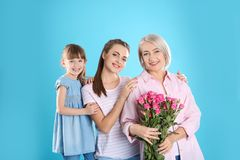 Beautiful mature lady, daughter and grandchild with flowers. Happy Women`s Day. Beautiful mature lady, daughter and grandchild with flowers on color background royalty free stock photo