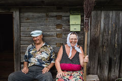 Beautiful mature russian couple have fun outside of their house in village. The woman clothed in a scarf keeps the broom Stock Photos