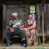 Beautiful mature russian couple have fun outside of their house in village. The woman clothed in a scarf keeps the broom Royalty Free Stock Images