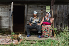 Beautiful mature russian couple have fun outside of their house in village. The woman clothed in a scarf keeps the broom Stock Image