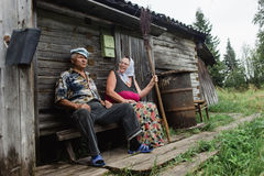 Beautiful mature russian couple have fun outside of their house in village. The woman clothed in a scarf keeps the broom Royalty Free Stock Photo