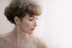 Beautiful mature topless woman. Standing by the window Stock Photography