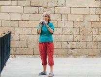 Beautiful mature tourist woman screens movie. Beautiful mature tourist woman travelling in Palma de Majorca screens movie on old video camera Stock Photography