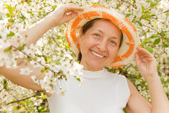 Beautiful mature woman. Woman aged stands in lush garden royalty free stock images