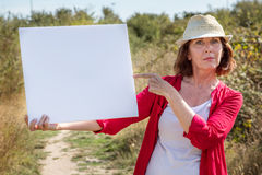 Beautiful mature woman alerting people with banner in sunny outdoors Stock Images