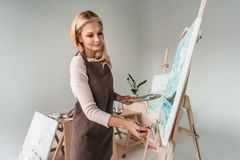 Beautiful mature woman in apron painting on easel at art. Class stock photos