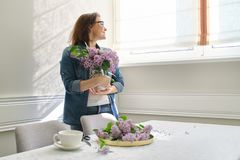 Free Beautiful Mature Woman At Home With Bouquet Of Lilac Flowers In Vase Drinking Cup Of Coffee Royalty Free Stock Image - 149054046
