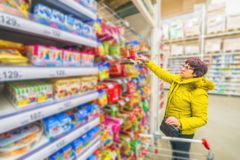 A beautiful mature woman is choosing goodies for her grandchildren in a supermarket. Russia Samara March 2019: A beautiful mature woman is choosing goodies for stock photos