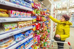 A beautiful mature woman is choosing goodies for her grandchildren in a supermarket. Russia Samara March 2019: A beautiful mature woman is choosing goodies for royalty free stock image