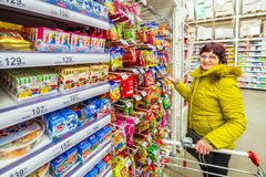 A beautiful mature woman is choosing goodies for her grandchildren in a supermarket. Russia Samara March 2019: A beautiful mature woman is choosing goodies for stock images