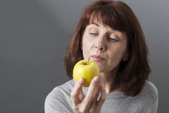 Beautiful mature woman contemplating yellow golden apple for vitamins diet. Diet and food concept - thoughtful 50s woman thinking about skin aging wondering Stock Photography