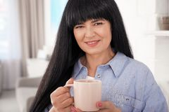 Beautiful mature woman with cup of drink stock photos