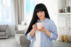 Beautiful mature woman with cup of drink stock photography