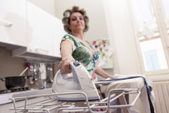Beautiful mature woman with curlers ironing Royalty Free Stock Image