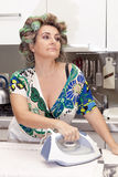 Beautiful mature woman with curlers ironing Stock Photo