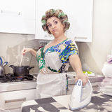 Beautiful mature woman with curlers ironing. Clothes at home Stock Photo