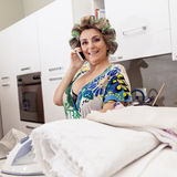 Beautiful mature woman with curlers ironing clothes at home Royalty Free Stock Images