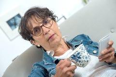 Beautiful mature woman drinking tea in the sofa. Beautiful mature woman drinking a tea in the sofa Stock Image