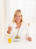 Beautiful mature woman enjoying a healthy cereals breakfast. Beautiful mature senior woman with shoulder length blond hair and a lovely smile enjoying a healthy Royalty Free Stock Photos