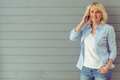 Beautiful mature woman with gadget Royalty Free Stock Photography