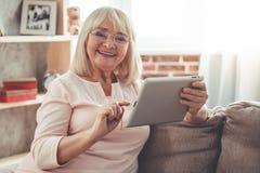 Beautiful mature woman with gadget Stock Photo