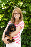 Beautiful mature woman in garden with puppy Stock Image