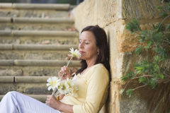 Beautiful mature woman in love with flower Royalty Free Stock Image