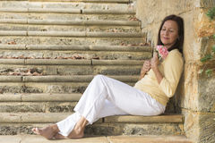 Beautiful mature woman in love with rose Stock Photo