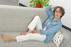 Beautiful mature woman lying on the couch Stock Photo