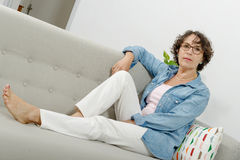 Beautiful mature woman lying on the couch Stock Images