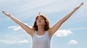 Beautiful mature woman opening her arms wide to the sky. Senior zen - thinking beautiful mature woman opening her chakra and arms wide,seeking for harmony and Royalty Free Stock Photo