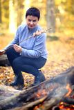 Camping in the forest. Beautiful mature woman on a picnic in the forest. A woman is cooking bacon on a fire, strung on a stick. Beautiful mature woman on a Stock Photos
