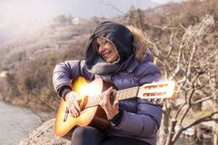 Beautiful mature woman playing a guitar sitting on a rock. In the mountains in a winter day Royalty Free Stock Photos
