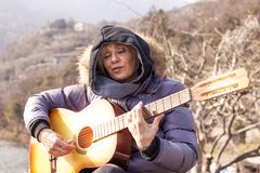 Beautiful mature woman playing a guitar sitting on a rock. In the mountains in a winter day Stock Images