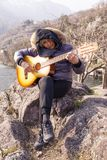 Beautiful mature woman playing a guitar sitting on a rock. In the mountains in a winter day Royalty Free Stock Images