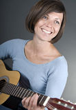 A beautiful mature woman plays guitar Royalty Free Stock Image