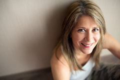 Beautiful mature woman with pleasing smile. Single beautiful mature woman in sleeveless blouse with long hair looking upward with pleasing smile and copy space Royalty Free Stock Image