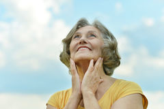 Beautiful mature woman. Posing against blue sky with clouds Stock Photography