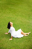 Beautiful mature woman. Relaxing in garden sit on the grass Royalty Free Stock Photo