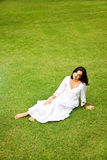 Beautiful mature woman. Relaxing in garden sit on the grass Royalty Free Stock Images