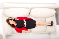 Beautiful mature woman relaxing on the sofa at home Stock Image