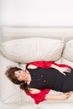 Beautiful mature woman relaxing on the sofa at home Royalty Free Stock Photos