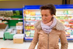 Beautiful mature woman shopping at the grocery store. Portrait of beautiful mature woman shopping at the grocery store in Finland Royalty Free Stock Image