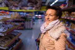 Beautiful mature woman shopping at the grocery store. Portrait of beautiful mature woman shopping at the grocery store in Finland Stock Photo